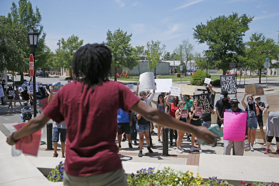 Photo - Protesters stand in front of the Edmond Police Department during a protest in Edmond, Okla., Saturday, June 6, 2020. The protest was organized in response to the shooting death of Isaiah Lewis by Edmond Police last year and the death of George Floyd in Minneapolis. [Bryan Terry/The Oklahoman]