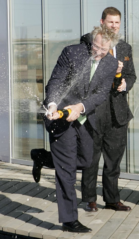 Photo -  From left, Aubrey McClendon, Chesapeake CEO and Clayton L. Bennett celebrate the opening of the Chesapeake Boathouse by spraying Champagne during the ceremony at the Oklahoma River, Jan. 17, 2006. Staff photo by Hugh Scott.