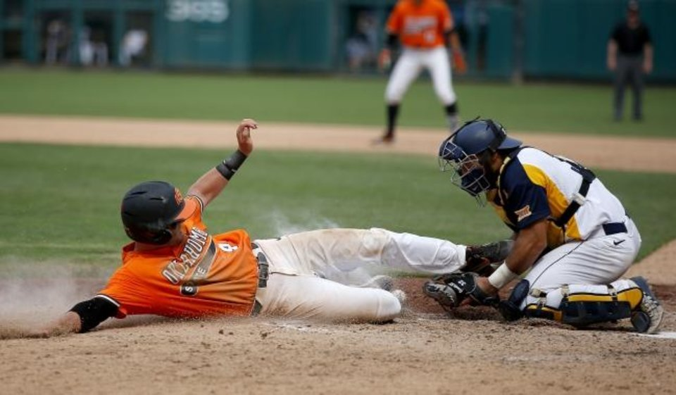 Photo -  Oklahoma State's Andrew Navigato, left, slides safely into home plate as West Virginia catcher Ivan Gonzalez loses the ball while trying to place the tag. The Cowboys beat the Mountaineers to win the Big 12 Tournament championship at Chickasaw Bricktown Ballpark.  [Sarah Phipps/The Oklahoman]