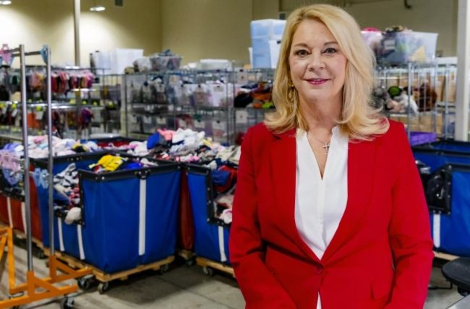 Photo -  Miki Farris, executive director of Infant Crisis Services, stands in front of mounds of donated clothing for infants and toddlers. [CHRIS LANDSBERGER/THE OKLAHOMAN]