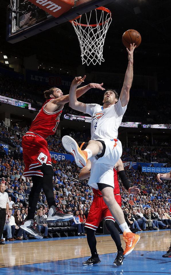 Photo - Oklahoma City's Nick Collison (4) makes a lay up as Chicago's Joakim Noah (13) defends during the NBA game between the Oklahoma City Thunder and the Chicago Bulls at Chesapeake Energy Arena in Oklahoma City, Sunday, March  15, 2015. Photo by Sarah Phipps, The Oklahoman
