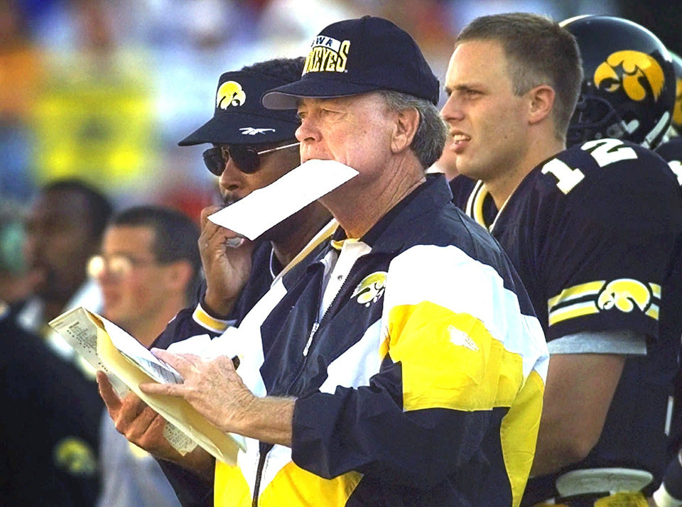 Photo - FILE-- University of Iowa football coach Hayden Fry, center, looks over his playbook during this1996 game with Iowa State in Iowa City, Iowa.  Despite a cushy nonconference schedule and a history of not playing well against the Buckeyes, Iowa coach Hayden Fry is optimistic going into  the Hawkeyes' game at No. 7 Ohio State on Saturday, Oct. 4, 1997.(AP Photo/Rodney White)