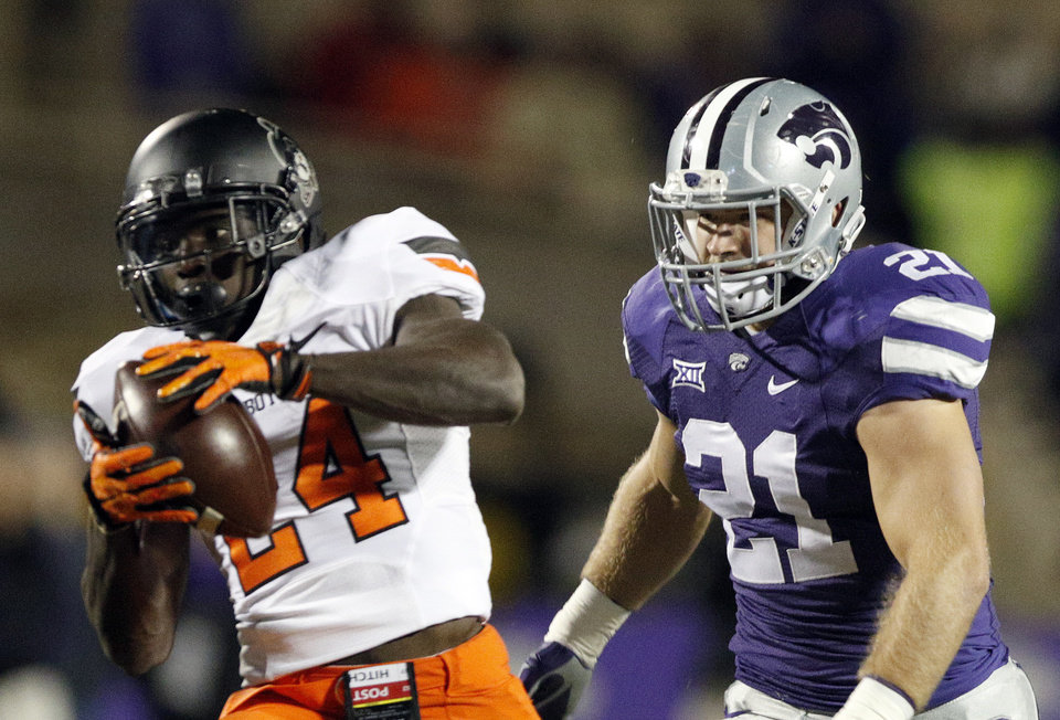 Photo - Oklahoma State's Tyreek Hill (24) makes a catch in front of Kansas State's Jonathan Truman (21) during the college football game between the Oklahoma State University Cowboys (OSU) and the Kansas State University Wildcats (KSU) Bill Snyder Family Stadium in Manhattan, Kan. on Friday, Jan. 3, 2014.  Photo by Sarah Phipps, The Oklahoman