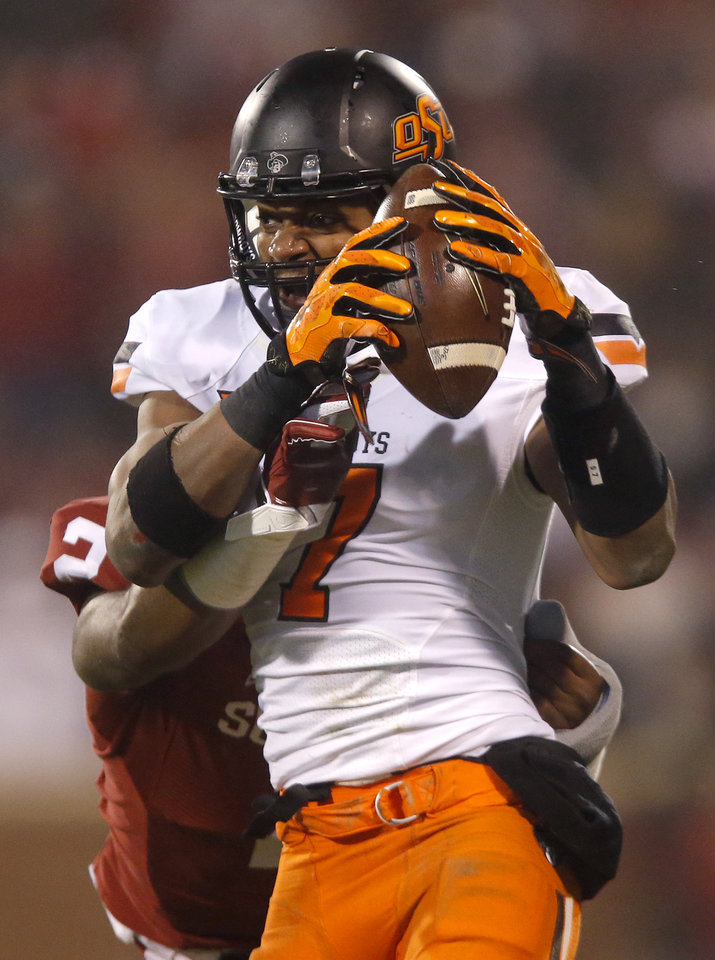 Photo - Oklahoma State's Brandon Sheperd (7) makes a catch as Oklahoma's Julian Wilson (2) defends during the Bedlam college football game between the University of Oklahoma Sooners (OU) and the Oklahoma State Cowboys (OSU) at Gaylord Family-Oklahoma Memorial Stadium in Norman, Okla., Saturday, Dec. 6, 2014. Photo by Sarah Phipps, The Oklahoman