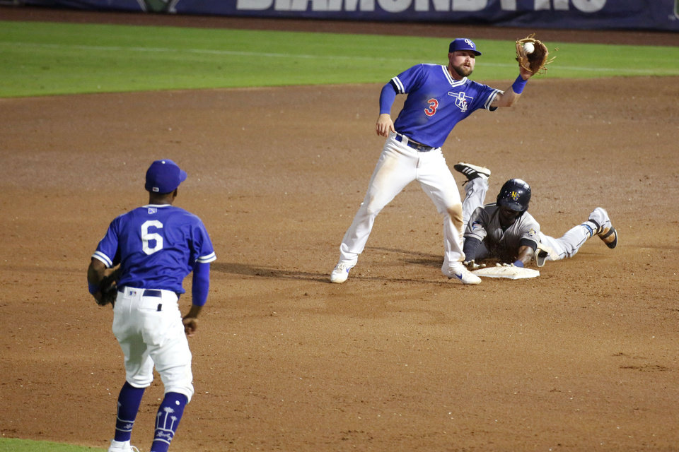 Photo - Jake Peter catches the ball as an opponent slides into second base during the Oklahoma City Dodgers game against the New Orleans Baby Cakes June 25, 2019. [Paxson Haws/The Oklahoman]