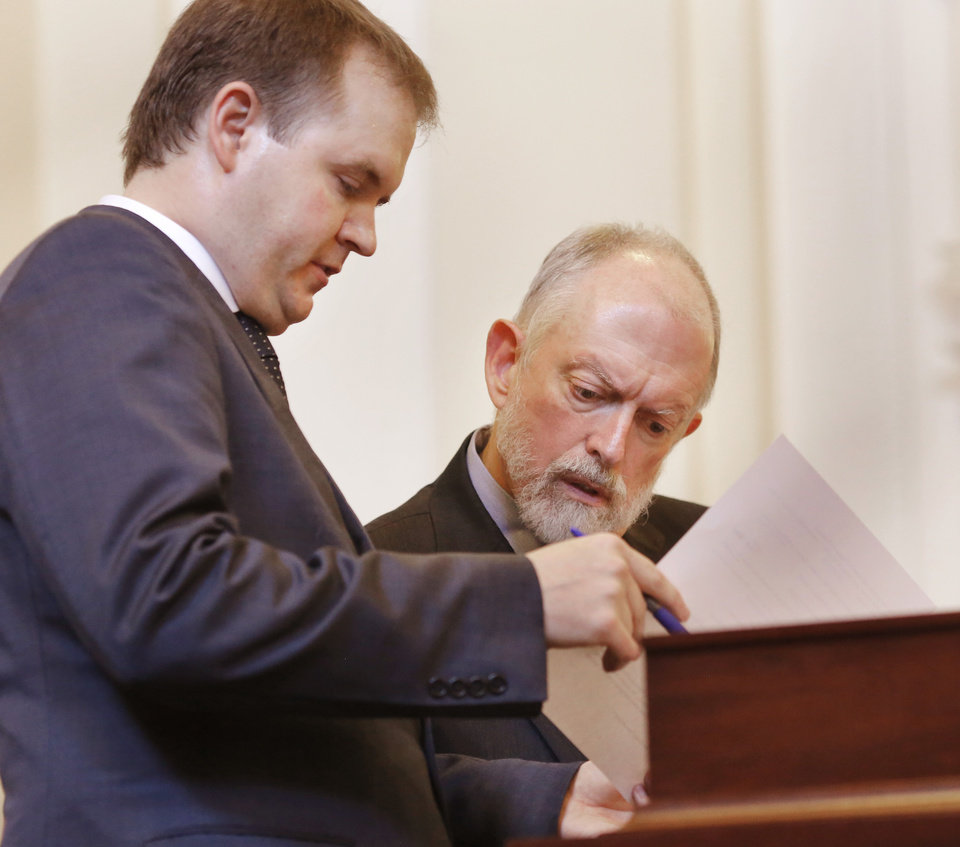 Photo - Garry Gaskins, left, attorney for Gentner Drummond, shows an evidentiary document to Bob Nance, one of two attorneys representing Mike Hunter. Oklahoma Attorney General Mike Hunter can remain on the ballot after the Oklahoma Election Board voted 3-0 on Monday, April 23, 2018, to deny a challenge to his candidacy on residency grounds. Hunter, a Republican, testified he always kept Oklahoma as his permanent home even though he lived in Virginia for years while working in Washington, D.C. for two trade organizations.