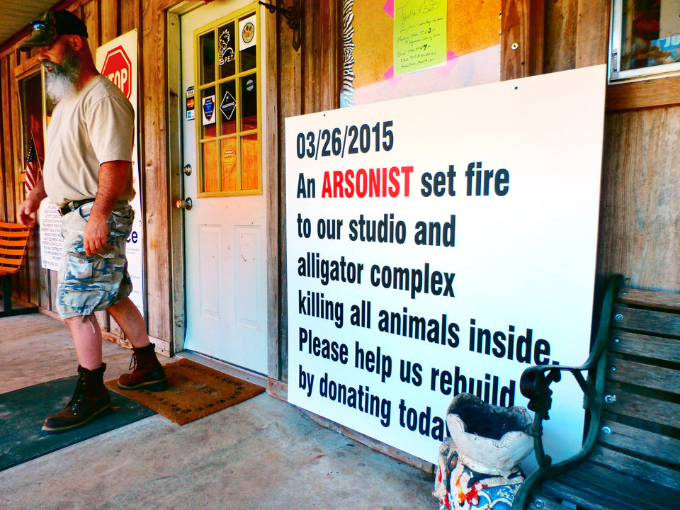 Photo -  A guest at the Garold Wayne Interactive Zoological Park in Wynnewood walks past a sign that describes a fire authorities believe was set on purpose last week. The photo was taken Tuesday, March 31, 2015. Photo by Andrew Knittle, The Oklahoman   Andrew Knittle