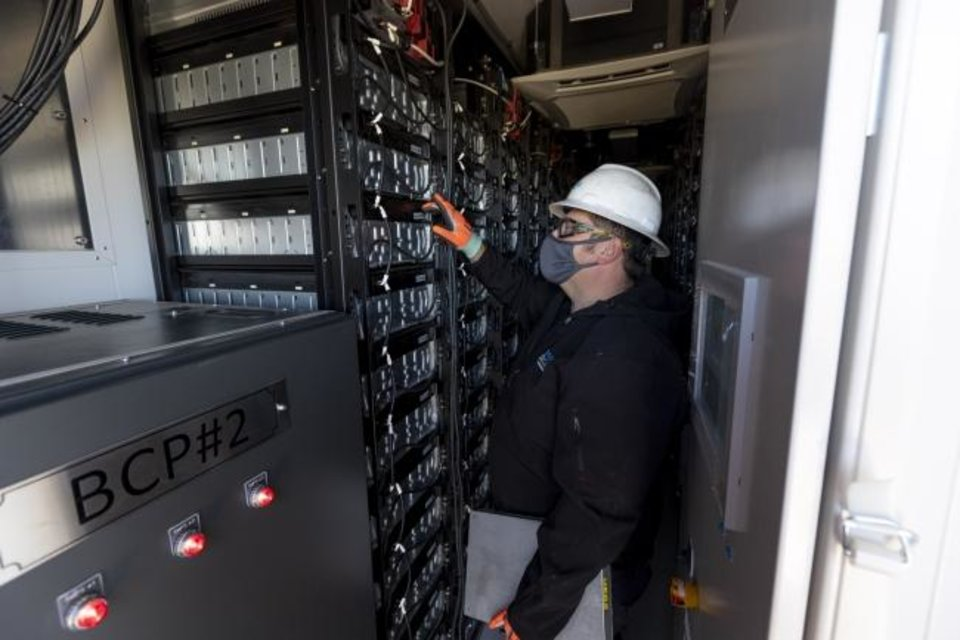 Photo -  NextEra Energy Resources' Chet Dysart inspects battery connections at the Rush Springs Energy Storage facility, co-located with the Rush Springs Wind Energy Center in Grady County. [PHOTO PROVIDED/NEXTERA ENERGY RESOURCES]
