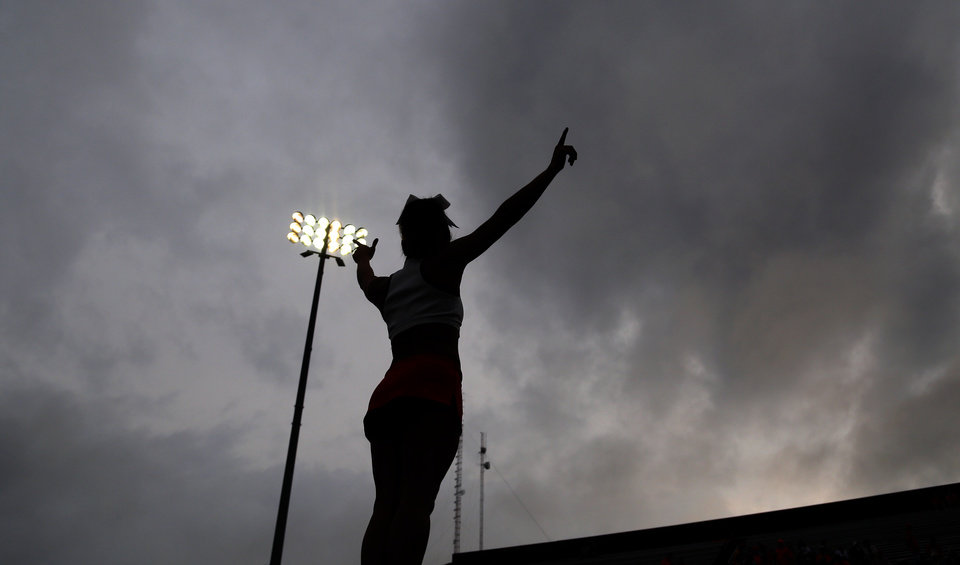 Photo - An Oklahoma State cheerleader performs during the college football game between the Central Michigan Chippewas and the Oklahoma State University Cowboys at the Kelly-Shorts Stadium in Mount Pleasant, Mich., Thursday, Sept. 3, 2015. Photo by Sarah Phipps, The Oklahoman