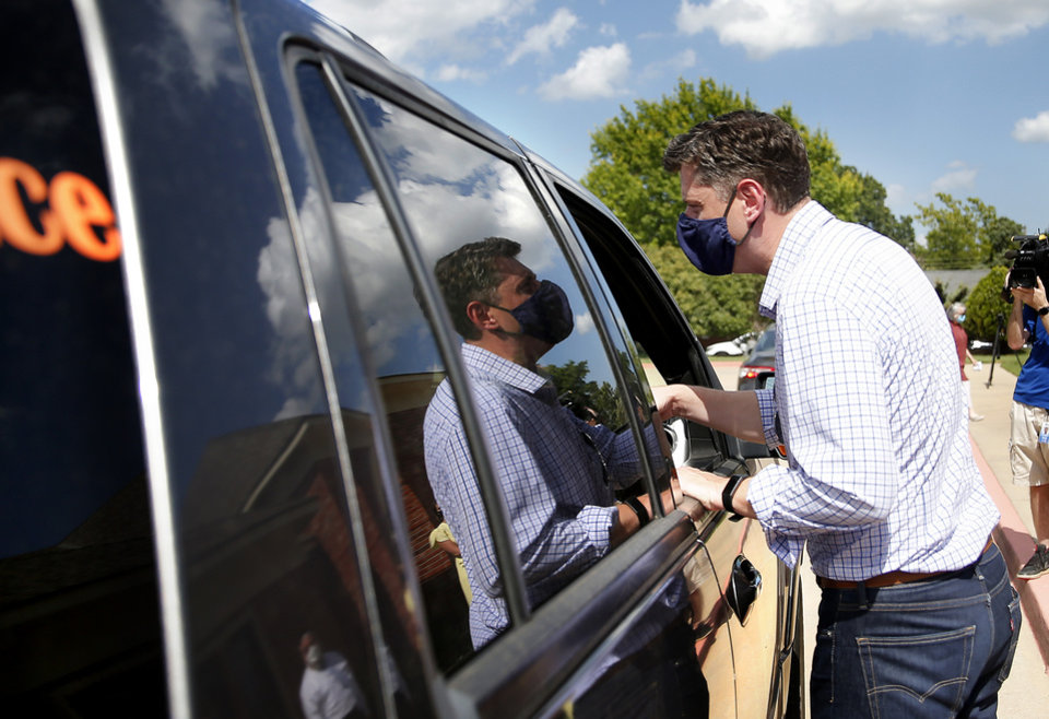 Photo - Mayor David Holt hands out a pack of masks during a free drive-thru mask distribution at the Chabad Community Center for Jewish Life & Learning in Oklahoma City, Wednesday, July 8, 2020. Photo by Sarah Phipps, The Oklahoman