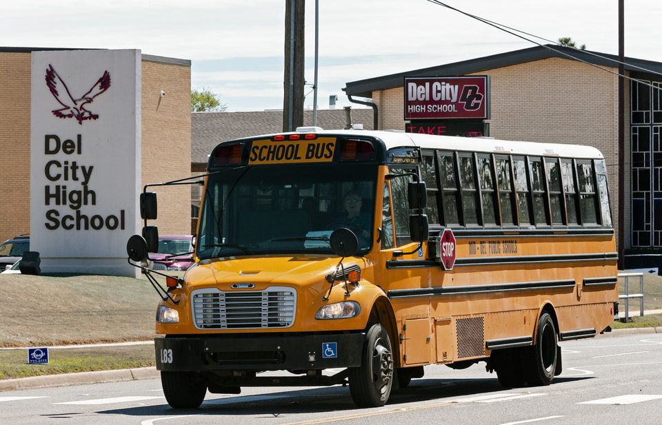 Photo - A school bus passes Del City High School in Del City, Okla. on Thursday, March 12, 2020.  Utah Jazz player Donovan Mitchell who tested positive for the coronavirus had a workout session at the school on Tuesday evening.  [Chris Landsberger/The Oklahoman]