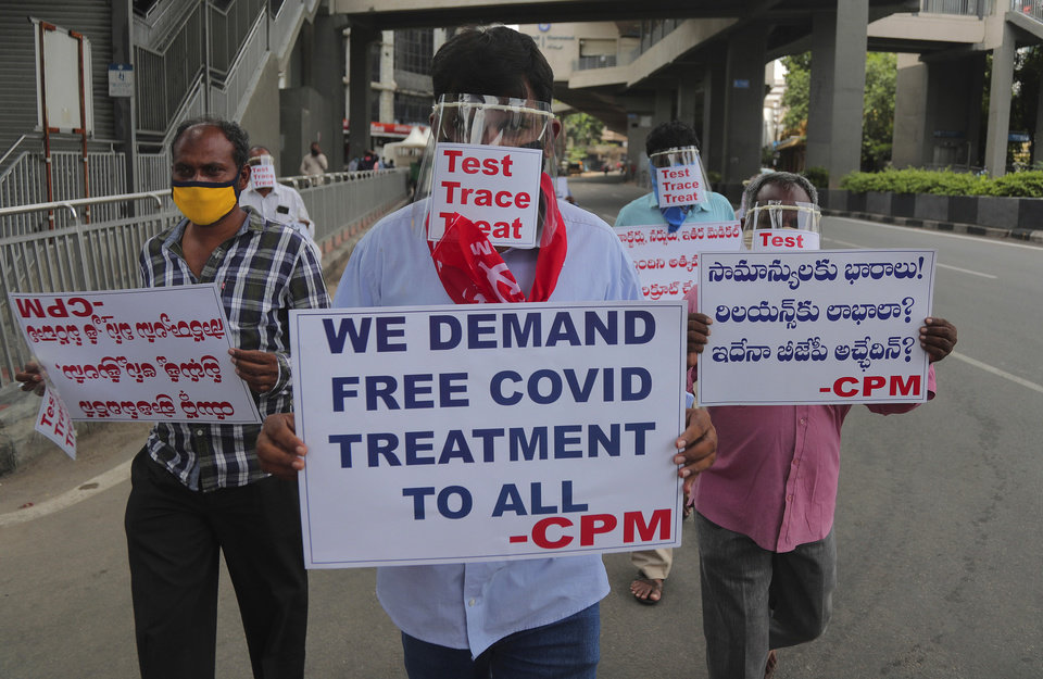 Photo -  Activists of Communist Party of India Marxist wearing face shields and hold placards during a protest asking the state government to increase testing and free treatment for all COVID-19 patients in Hyderabad, India, Monday, June 29, 2020. Governments are stepping up testing and warily considering their next moves as the number of newly confirmed coronavirus cases surges in many countries. India reported more than 20,000 new infections on Monday.  (AP Photo/Mahesh Kumar A.)
