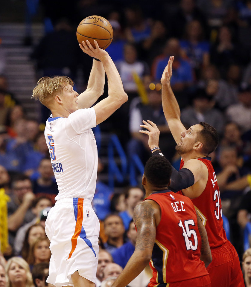 Photo - Oklahoma City's Kyle Singler (5) shoots against New Orleans' Alonzo Gee (15) and Ryan Anderson (33) during an NBA basketball game between the New Orleans Pelicans and the Oklahoma City Thunder at Chesapeake Energy Arena in Oklahoma City, Thursday, Feb. 11, 2016. Oklahoma City won 121-95. Photo by Nate Billings, The Oklahoman
