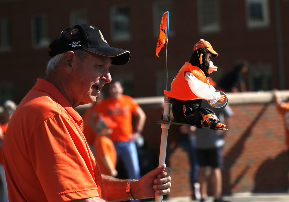 Photo - A fan carries a toy monkey during the walk before the college football game between the Oklahoma State Cowboys and the Kansas State Wildcats at Boone Pickens Stadium in Stillwater, Okla., Saturday, Sept. 28, 2019. [Sarah Phipps/The Oklahoman]