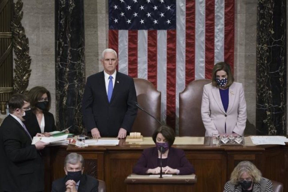 Photo -  Vice President Mike Pence and Speaker of the House Nancy Pelosi, D-Calif., read the final certification of Electoral College votes cast in November's presidential election during a joint session of Congress after working through the night, at the Capitol in Washington, Thursday, Jan. 7, 2021. Violent protesters loyal to President Donald Trump stormed the Capitol Wednesday, disrupting the process. (AP Photo/J. Scott Applewhite, Pool)