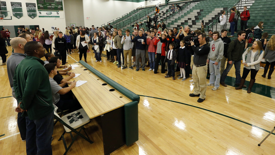 Photo - Trevor Magee, John Kolar and Bo Garver make their college intentions known at Norman North High School on Wednesday, Feb. 4, 2015  in Norman, Okla. Photo by Steve Sisney, The Oklahoman