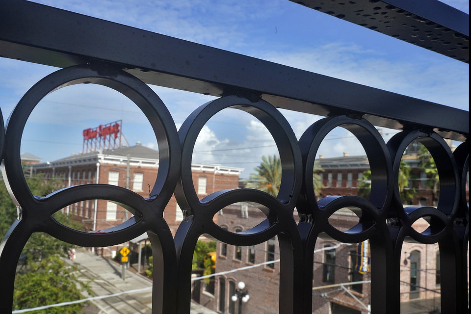 Photo -  Wrought Iron railings on a balcony at the Hotel Haya overlooking Ybor Square is shown Monday, Aug. 31, 2020, in Tampa, Fla. When the pandemic hit, the Aparium group was deep into construction on six new hotels, too far to turn back, yet keenly aware that timelines would be significantly derailed and room occupancy and dining projections would be far fewer, cutting into profit margins by millions.   (AP Photo/Chris O'Meara)