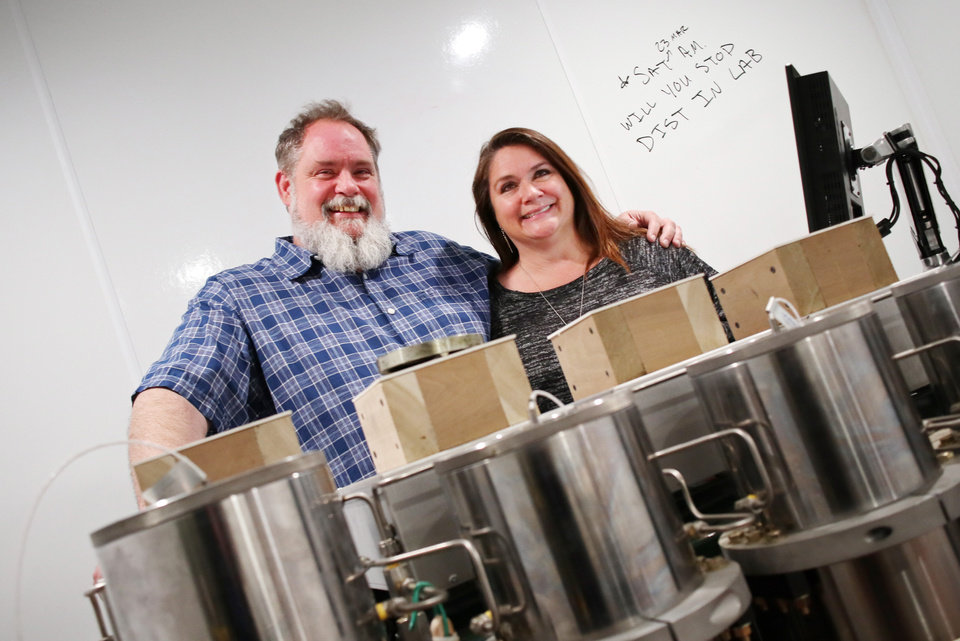 Photo -  Red Dirt Labs co-owners Tommy Gragg and Shelly Gragg stand behind lab equipment at their business.