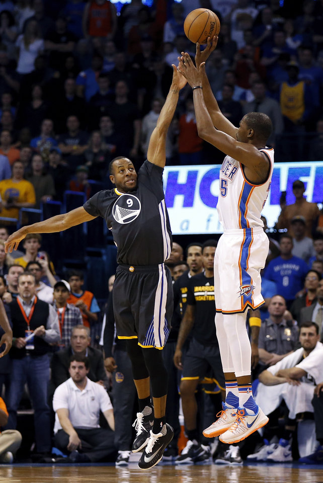 Photo - Oklahoma City's Kevin Durant (35) takes a 3-point shot over Golden State's Andre Iguodala (9) to give Oklahoma City a 103-99 lead with 14.5 seconds in the fourth quarter during an NBA basketball game between the Oklahoma City Thunder and the Golden State Warriors at Chesapeake Energy Arena in Oklahoma City, Saturday, Feb. 27, 2016. Golden State won 121-118 in overtime. Photo by Nate Billings, The Oklahoman