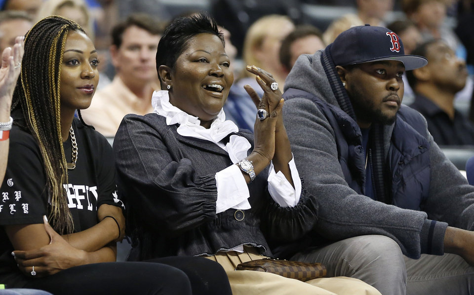 Photo - Wanda Pratt, center, Kevin Durant's mother, applauds Tuesday as she sits between Tony Durant, right, Kevin's brother, and Kevin's fiancee, Monica Wright, left, during the second quarter of the Thunder's preseason game against the Denver Nuggets in Oklahoma City. AP PHOTO
