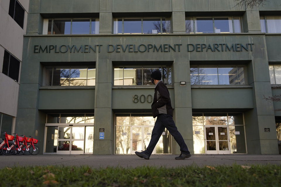 Photo -  In this Dec. 18, 2020, file photo, a person passes the office of the California Employment Development Department in Sacramento, Calif. On Tuesday, Jan. 26, 2021, California State Auditor Elaine Howle released a report saying that the EDD might have overpaid millions of people since March 2020 after it stopped enforcing eligibility rules so they could process claims faster. [AP Photo/Rich Pedroncelli, File]