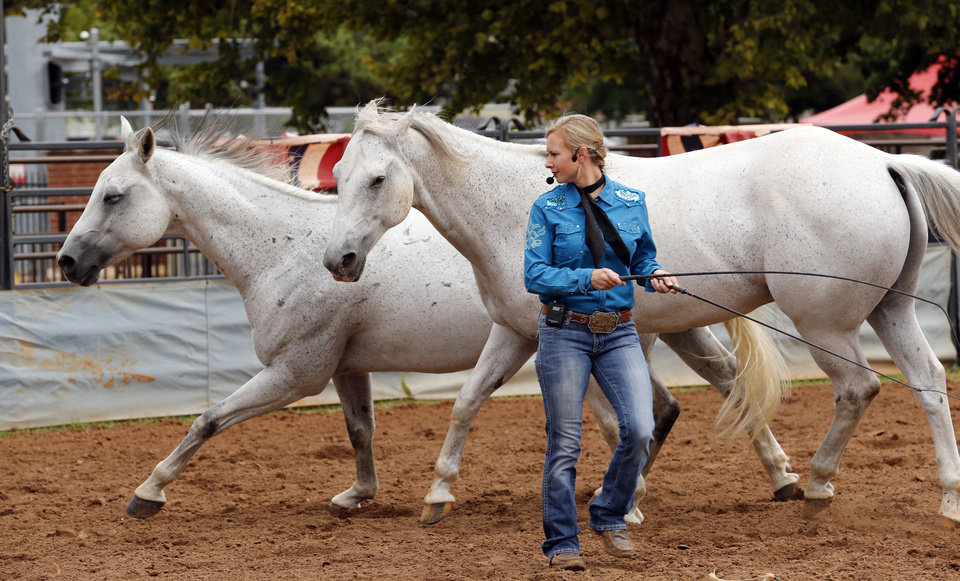 Photo -  Jessica Blair Fowlkes, with Liberty Riders, shows horse training skills at the Oklahoma State Fair on Thursday.