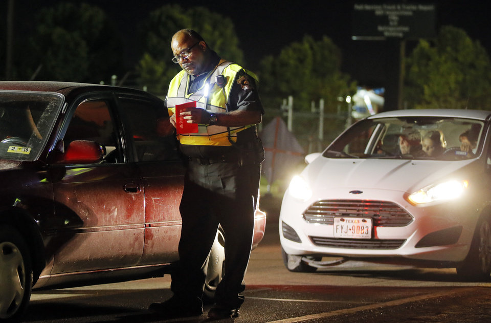 Photo - Oklahoma County Sheriff's Deputy Marvin Sampson works an ENDUI checkpoint on westbound Reno Ave. just east of Rockwell Ave. in Oklahoma City, Saturday, Aug. 13, 2016. Photo by Nate Billings, The Oklahoman