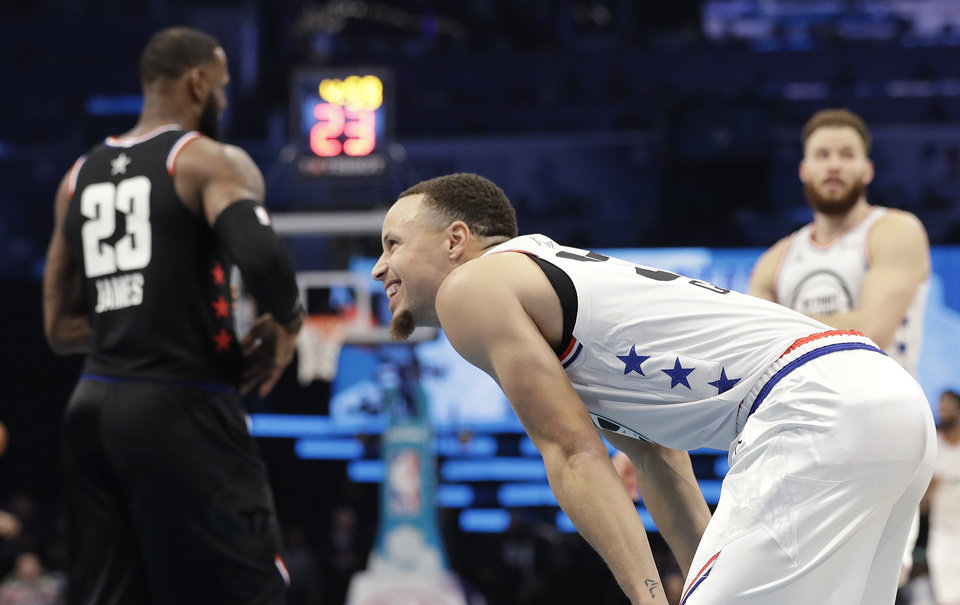 Photo - Team Giannis' Stephen Curry, of the Golden State Warriors smiles on the court as Team LeBron's LeBron James, of the Cleveland Cavaliers, looks on during the first half of an NBA All-Star basketball game, Sunday, Feb. 17, 2019, in Charlotte, N.C. (AP Photo/Chuck Burton)