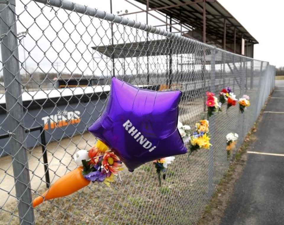 Photo -  Flowers, balloons and personalized notes are placed on a chain-link fence near the home dugout of the Konawa softball stadium.   Monday, March 11, 2019. .Photo by Jim Beckel, The Oklahoman.