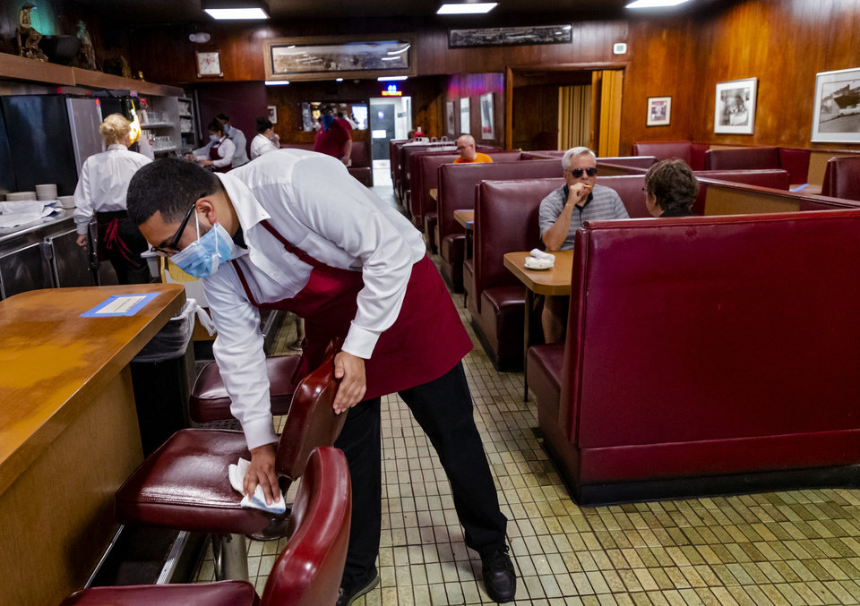 Photo - Waiter Josh Mijares sanitizes a seat for customers during lunch at Cattlemen's Steakhouse in Oklahoma City, Okla. on Friday, May 1, 2020. Cattlemen's and other restaurants begin their gradual reopening on Friday after being closed due to the Coronavirus Pandemic.[Chris Landsberger/The Oklahoman]