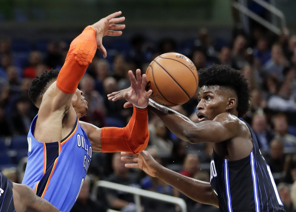 Photo - Oklahoma City Thunder's Russell Westbrook, left, loses the ball as he is fouled by Orlando Magic's Jonathan Isaac during the first half of an NBA basketball game, Tuesday, Jan. 29, 2019, in Orlando, Fla. (AP Photo/John Raoux)
