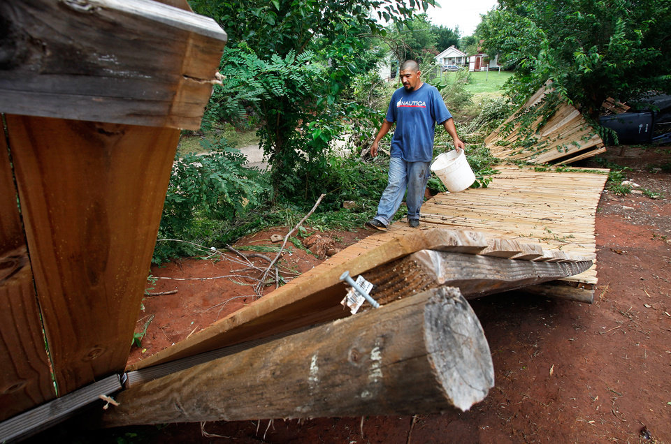 Photo - Abel Borrego walks along the edge of the toppled fence that separated his back yard from Lightning Creek. Borrego's home, on the east bank of the creek,   near SW 28 and Santa Fe, sustained damage from the rushing waters of last night's flooding. Residents cleaned homes and yards in the area near Lightning Creek in south Oklahoma City, Friday, July 9, 2010. Heavy rains last night caused the  creek to overflow its banks, flooding the areas on both sides of the creek.  Staff Photo by Jim Beckel , The Oklahoman