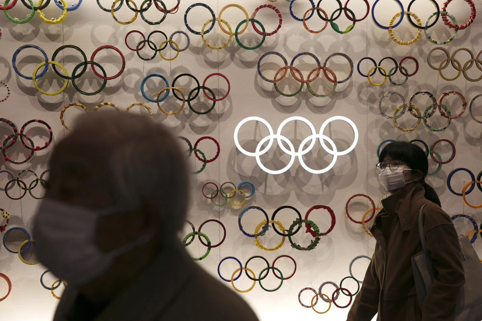 Photo - FILE - In this Feb. 23, 2020, file photo, two people wear masks as they visit the newly opened Japan Olympic Museum located near the New National Stadium in Tokyo. The Olympic flame from Greece is set to arrive in Japan even as the opening of the the Tokyo Games in four months is in doubt with more voices suggesting the games should to be postponed or canceled because of the worldwide virus pandemic. (AP Photo/Jae C. Hong, File)