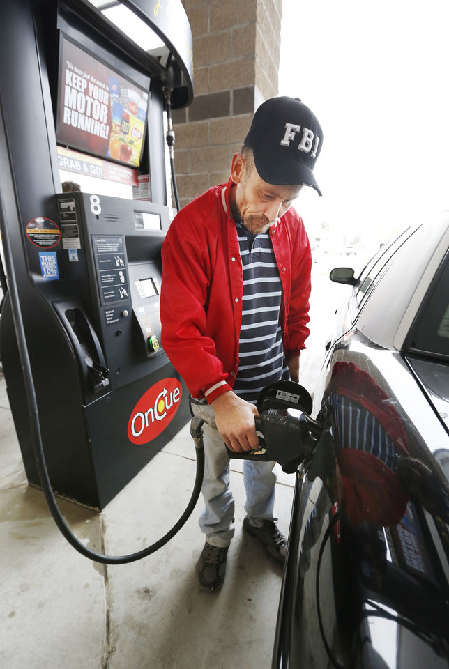 Photo -  David Rupert gets gasoline at the OnCue, SE 44 and Shields Boulevard. Oklahomans are seeing higher gasoline prices. [Photo by Paul B. Southerland, The Oklahoman Archives]