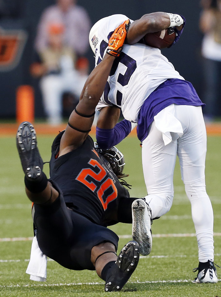 Photo - Oklahoma State's Jordan Burton (20) brings down TCU's KaVontae Turpin during a November football game between the Cowboys and Horned Frogs at Boone Pickens Stadium in Stillwater. OSU won, 49-29. Photo by Nate Billings, The Oklahoman