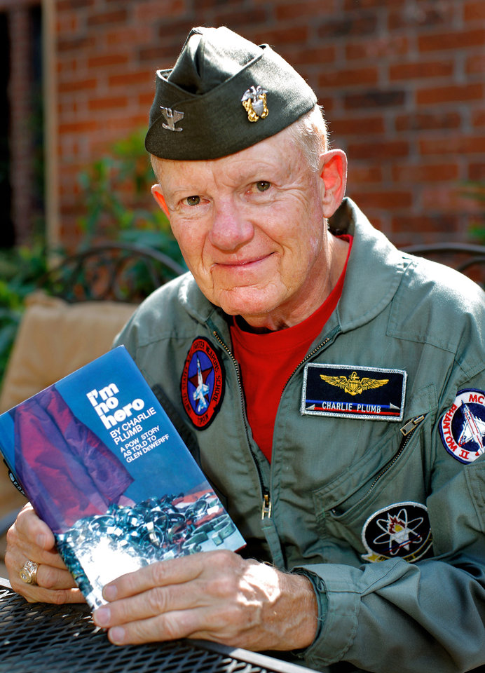 Photo -  Retired US Navy Capt. Charlie Plumb holds a copy of his book, 'I'm No Hero,