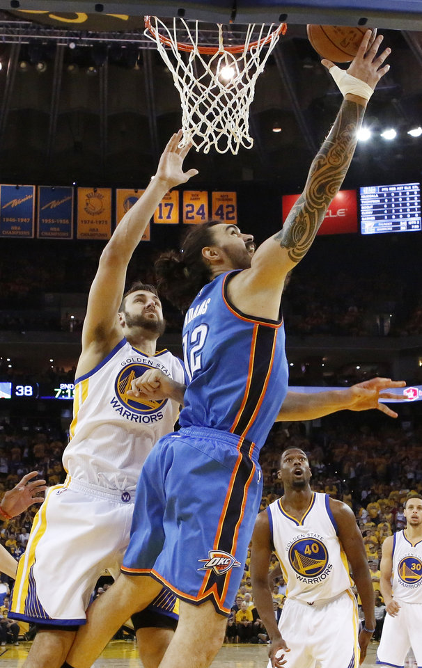 Photo - Oklahoma City's Steven Adams (12) shoots in front of Golden State's Andrew Bogut (12) during Game 5 of the Western Conference finals in the NBA playoffs between the Oklahoma City Thunder and the Golden State Warriors at Oracle Arena in Oakland, Calif., Thursday, May 26, 2016. The Warriors won 120-111. Photo by Nate Billings, The Oklahoman