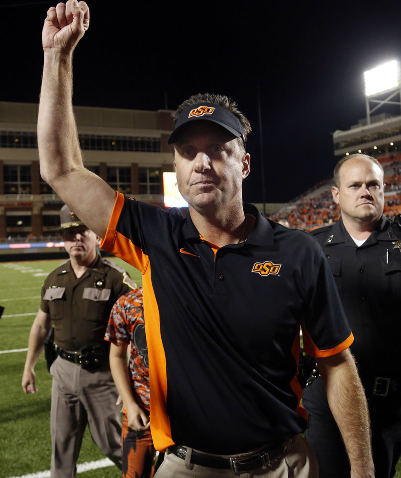 Photo - Oklahoma State head coach Mike Gundy acknowledges the fans following the college football game between the Oklahoma State Cowboys (OSU) and TCU Horned Frogs at Boone Pickens Stadium in Stillwater, Okla., Saturday, Nov. 7, 2015. Photo by Sarah Phipps, The Oklahoman