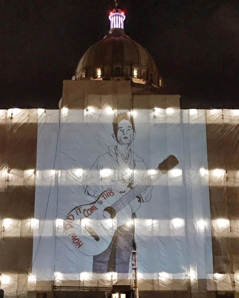 Photo -  An image of Woody Guthrie is projected on Monday onto a construction tarp draped across the Oklahoma Capitol. [Photo provided by Jack Fowler]