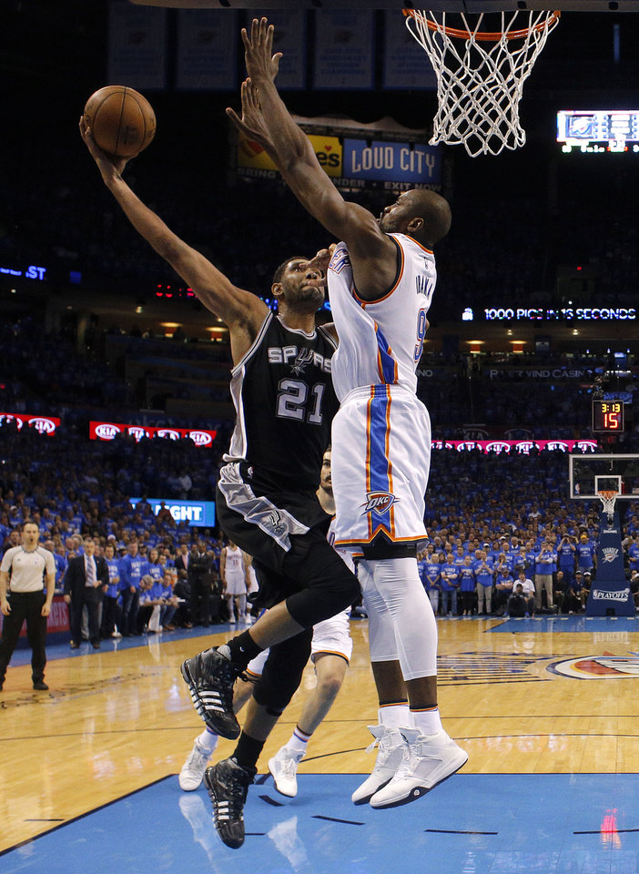 Photo - Oklahoma City's Serge Ibaka (9) blocks the shot of San Antonio's Tim Duncan (21) in the fourth quarter during Game 6 of the Western Conference semifinals between the Oklahoma City Thunder and the San Antonio Spurs in the NBA playoffs at Chesapeake Energy Arena in Oklahoma City, Thursday, May 12, 2016. Photo by Sarah Phipps, The Oklahoman