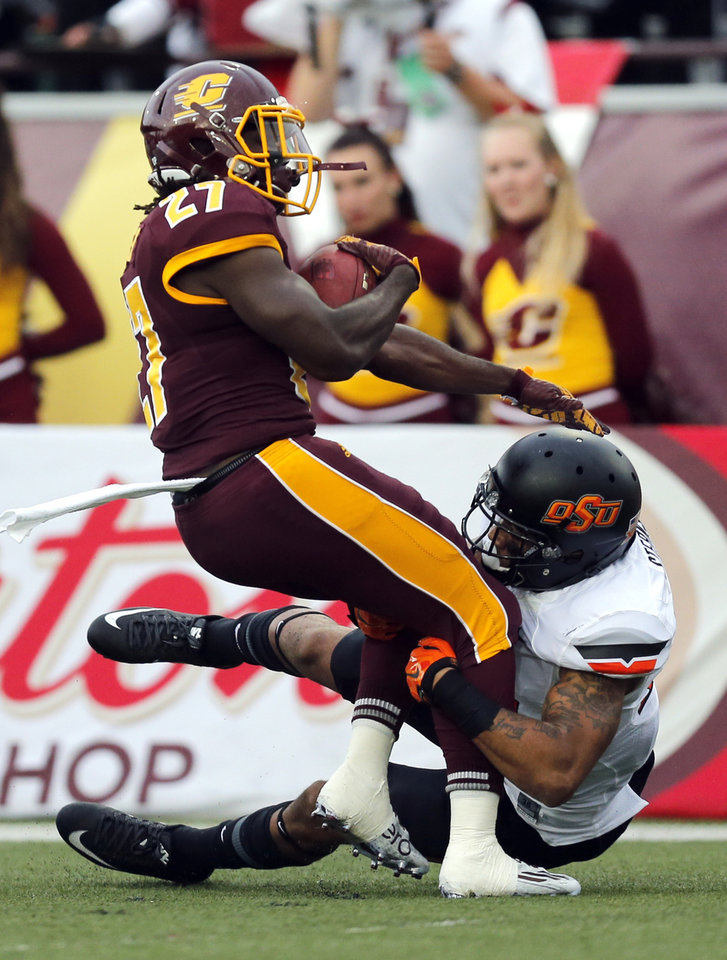 Photo - Oklahoma State's Jordan Sterns (13) brings down Central Michigan's Martez Walker (27) during the college football game between the Central Michigan Chippewas and the Oklahoma State University Cowboys at the Kelly-Shorts Stadium in Mount Pleasant, Mich., Thursday, Sept. 3, 2015. Photo by Sarah Phipps, The Oklahoman