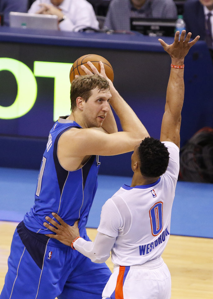 Photo - Dallas Mavericks forward Dirk Nowitzki, left, looks to pass as Oklahoma City Thunder guard Russell Westbrook defends during the second half of Game 2 of a first-round NBA playoff series on Monday in Oklahoma City. Dallas won 85-84. (AP Photo)