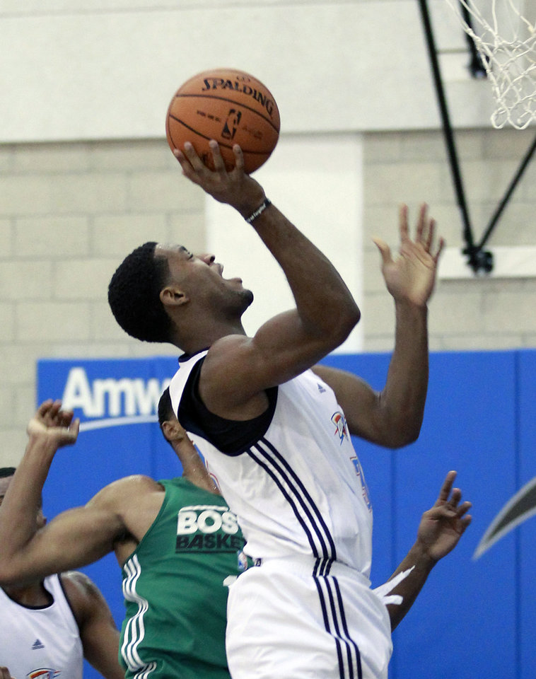 Photo - Oklahoma City Thunder's Perry Jones, right, shoots in front of Boston Celtic's Fab Melo during an NBA summer league basketball game, Monday, July 9, 2012, in Orlando, Fla. (AP Photo/John Raoux) ORG XMIT: DOA109