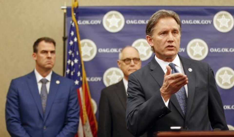 Photo -  Oklahoma Attorney General Mike Hunter speaks in front of Gov. Kevin Stitt, left, and Rep. Harold Wright during a press conference Thursday announcing plans for Oklahoma to resume executions by lethal injection. [Nate Billings/The Oklahoman]