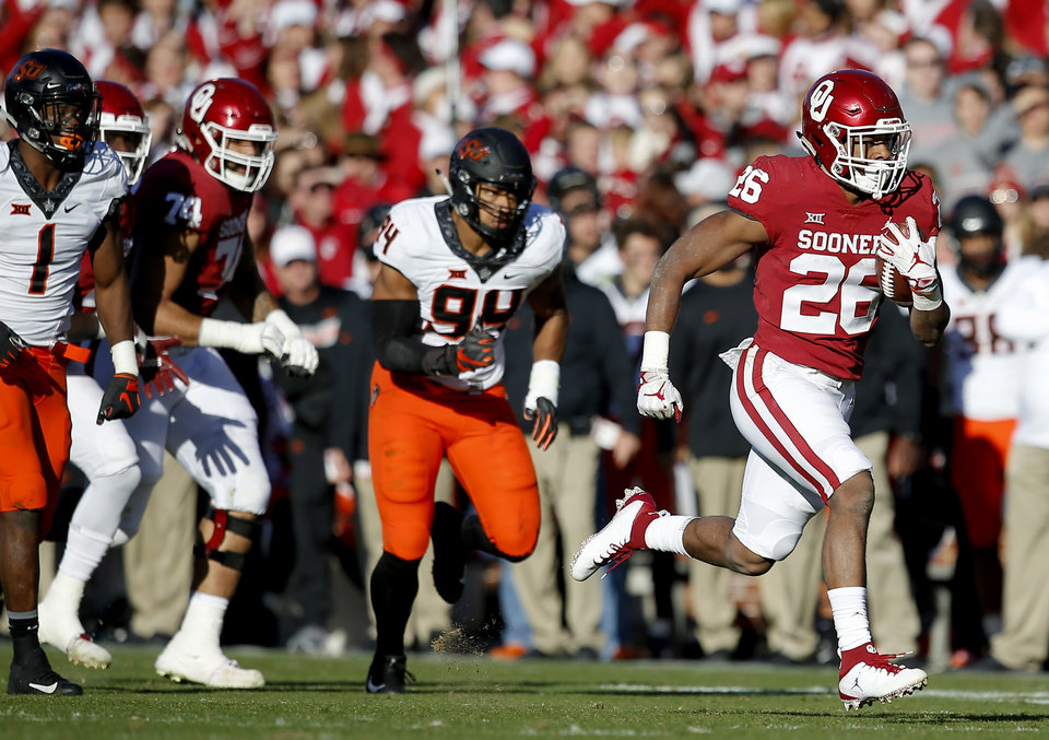 Photo - Oklahoma's Kennedy Brooks (26) rushes in the first quarter during a Bedlam college football game between the University of Oklahoma Sooners (OU) and the Oklahoma State University Cowboys (OSU) at Gaylord Family-Oklahoma Memorial Stadium in Norman, Okla., Nov. 10, 2018.  OU won 48-47. Photo by Sarah Phipps, The Oklahoman