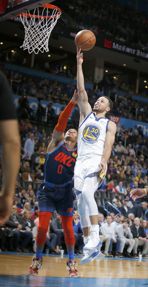 Photo - Golden State's Stephen Curry (30) goes up for a lay up as Oklahoma City's Russell Westbrook (0) defends during the NBA basketball game between the Oklahoma City Thunder and the Golden State Warriors at Chesapeake Energy Arena,  Saturday, March 16, 2019. Photo by Sarah Phipps, The Oklahoman