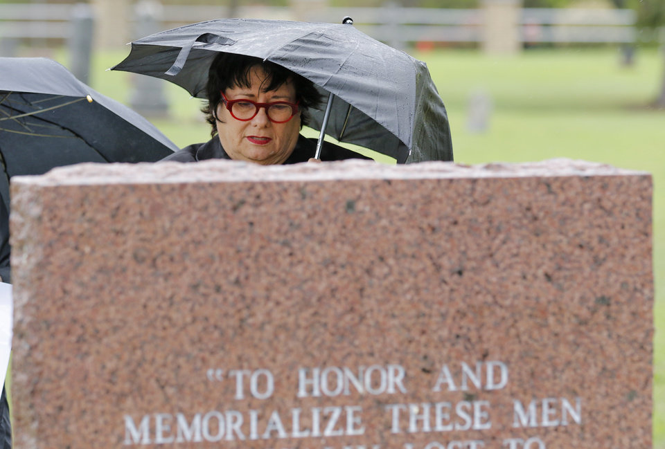 Photo -  Patty Somade looks at a memorial with the names of 39 people who died in the 1918 fire at Griffin Memorial Hospital. The service was Monday at the IOOF Cemetery in Norman. Photo By Steve Gooch, The Oklahoman   Steve Gooch -  The Oklahoman