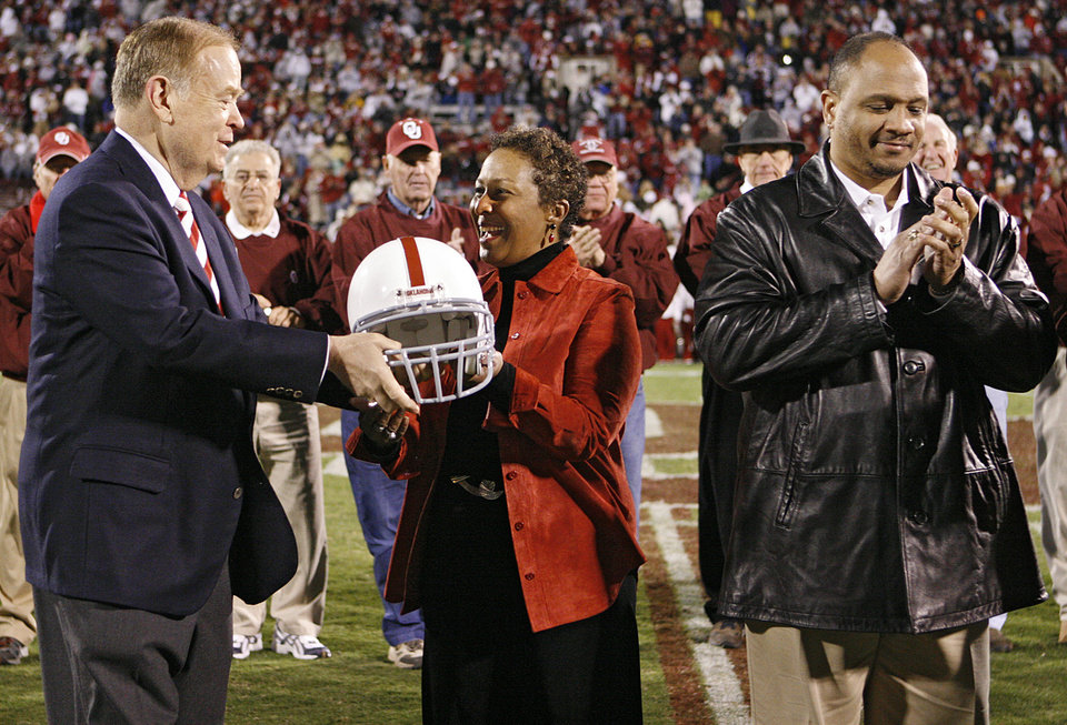 Photo - ROGER GAUTT: University of Oklahoma president David Boren, left, hands a helmet to Sandra Gautt as her son Roger stands at right during a halftime honor for Gautt's husband Prentice Gautt, who was the first black player to make the Sooner football team 50 years ago in the University of Oklahoma Sooners (OU) college football game against Colorado University (CU) at the Gaylord Family - Oklahoma Memorial Stadium, on Saturday, Oct. 21, 2006, in Norman, Okla.   By Bryan Terry, The Oklahoman  ORG XMIT: KOD
