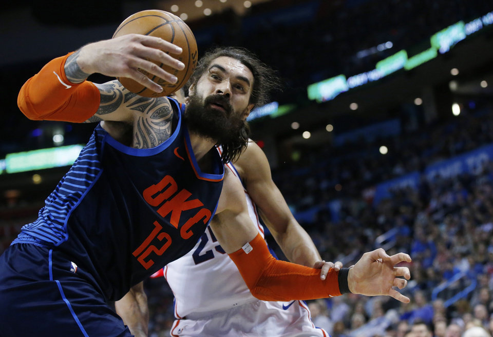Photo - Oklahoma City Thunder center Steven Adams (12) reaches for the ball in front of Philadelphia 76ers guard Ben Simmons during the second half of an NBA basketball game Thursday, Feb. 28, 2019, in Oklahoma City. (AP Photo/Sue Ogrocki)