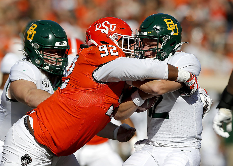 Photo - Oklahoma State's Cameron Murray (92) sacks Baylor's Charlie Brewer (12) in the first quarter during the college football game between Oklahoma State University and Baylor at Boone Pickens Stadium in Stillwater, Okla., Saturday, Oct. 19, 2019. [Sarah Phipps/The Oklahoman]